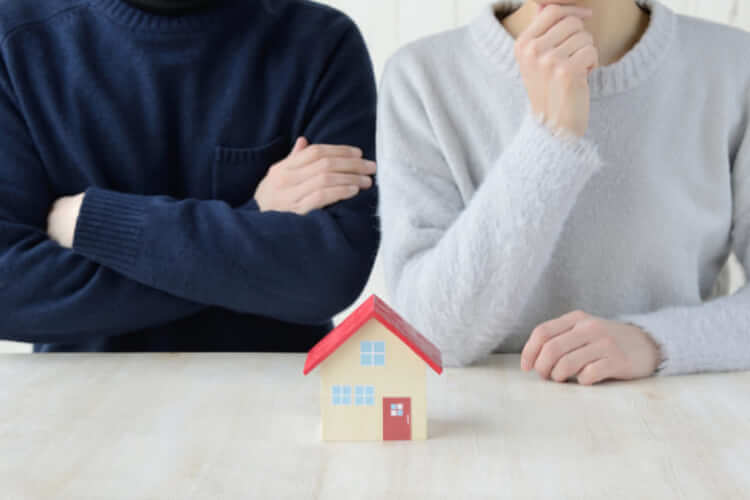 夫婦が家の模型の前で悩んでいる